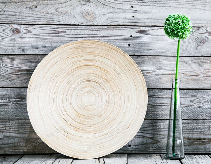 beautiful vase on a wooden plate with a flower on a wooden background