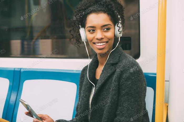 Happy young black woman sitting inside the underground listening to music