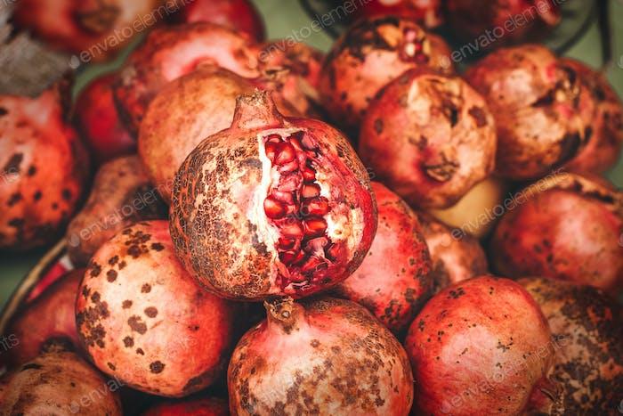 Ripe pomegranate fruits on the market shelf, Overripe burst Garnet lies on top