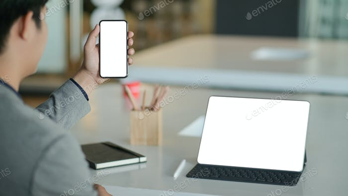 Young businessman hold a blank screen smartphone in hand and a blank screen laptop on the desk.