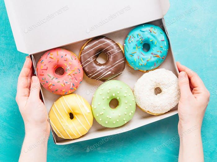 Hände halten Box mit Donuts