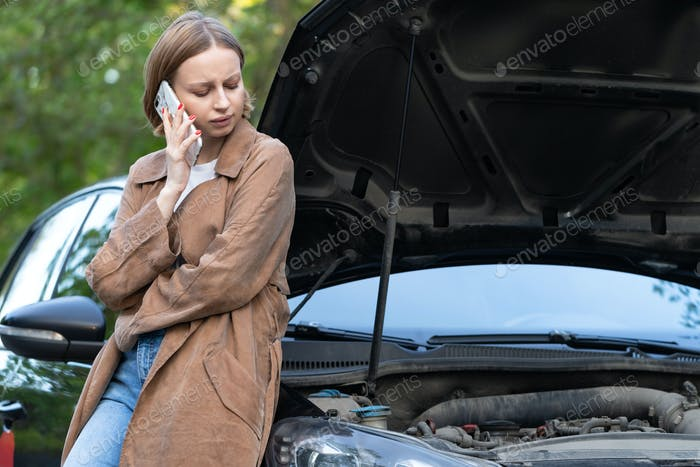 Helpless woman driver calling for help/assistance looking at broken down car, stopped at roadside