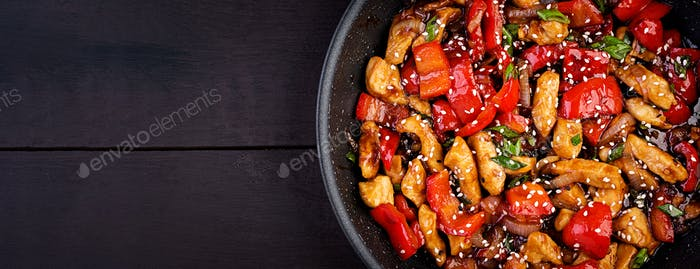 Stir fry chicken, sweet peppers and green onion. Top view. Banner. Asian cuisine