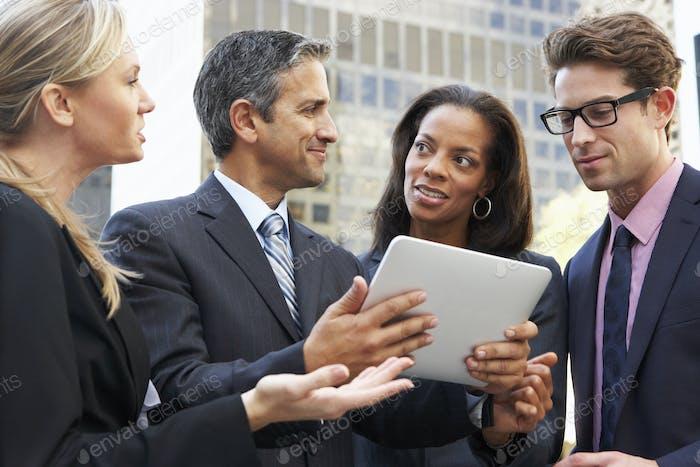 Geschäftsleute und Geschäftsfrauen mit Digital-Tablet-Außenseite