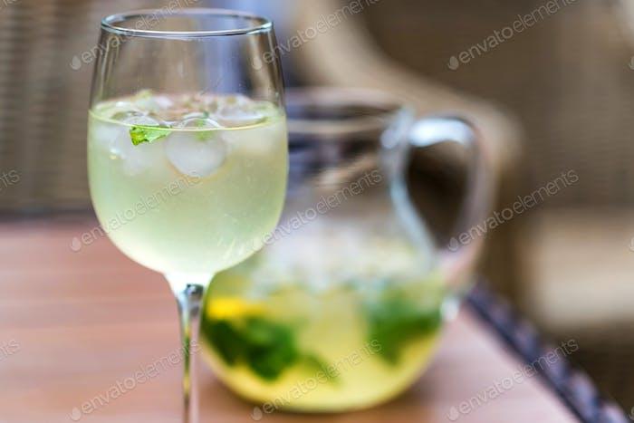 Erfrischender Mojito Cocktail in Glas und Krug schließen