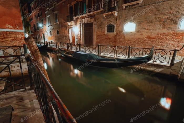 Venice Gondola boat in small channel in lagoon city Venice at night. Long exposure Venezia Italy