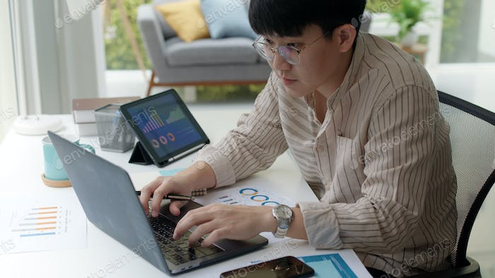 Asia people happy man coding on laptop work remotely at home office