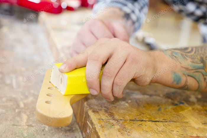 Carpenter sanding a guitar neck in wood at workshop
