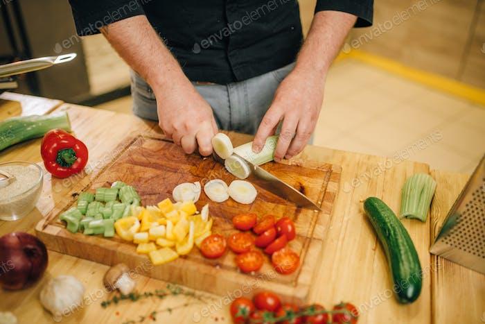 Chef mit Messer schneidet Pilze auf Holzbrett