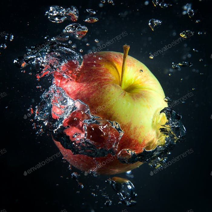 Apple is under water in a stream of air bubbles