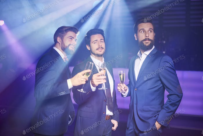Three gentlemans in suit at night club