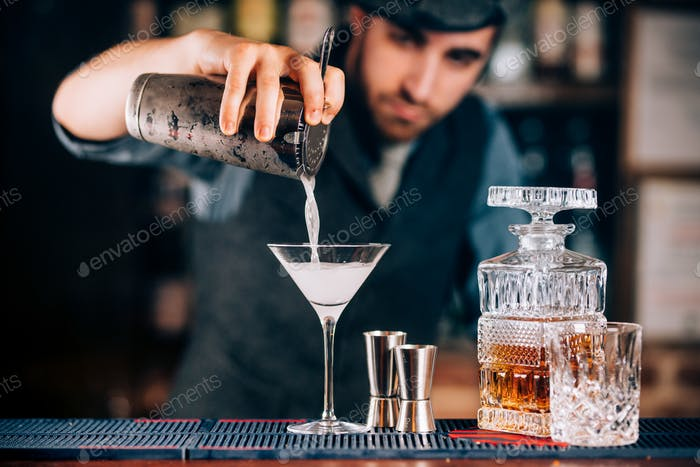 Martini preparation. Dry martini details, close up of alcoholic beverage at bar