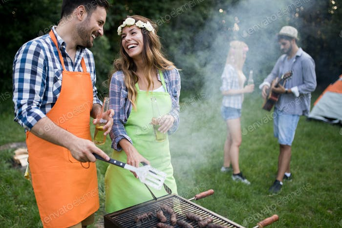 Young couple with friends smiles and making roasted barbecue in campground