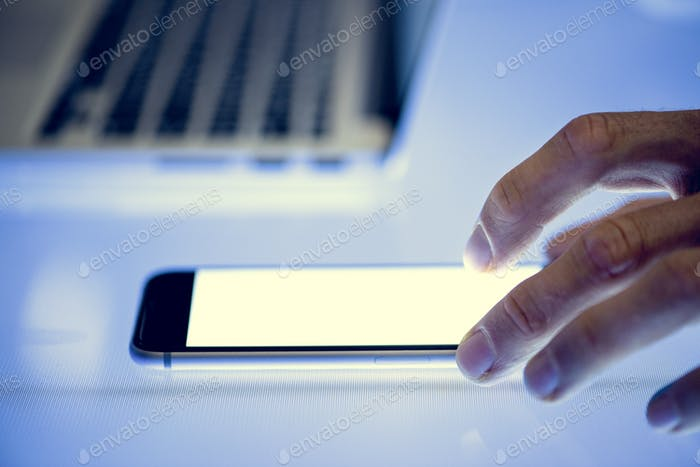 Hand using smartphone with laptop on the side