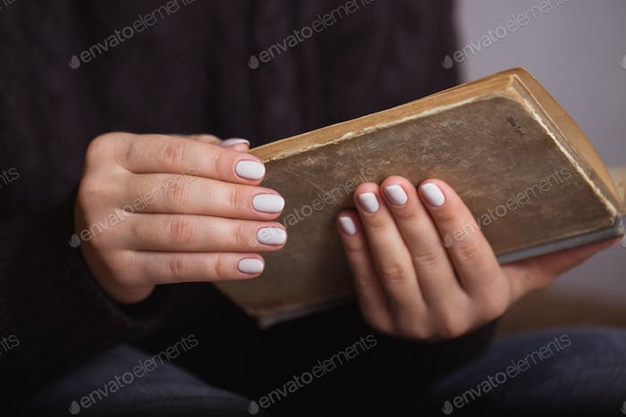 Woman with beautiful manicure holding an old book