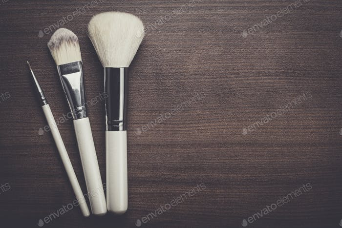 white make-up brushes on brown background