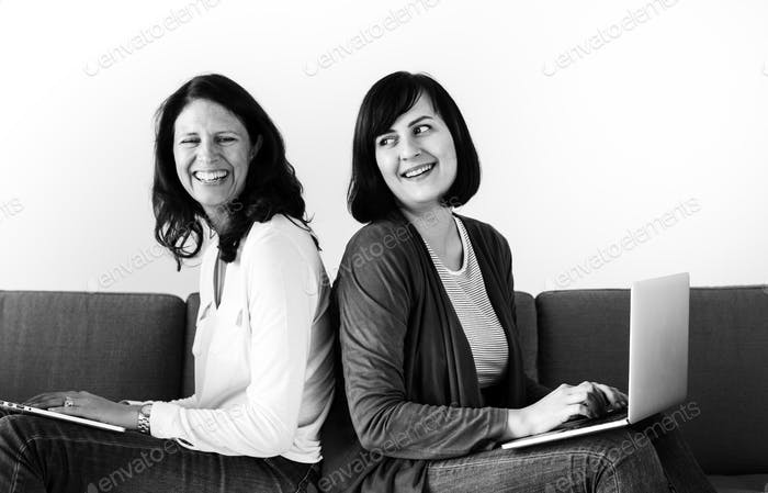 Women using laptop on sofa together