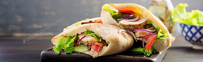 Pita stuffed with chicken, tomato and lettuce on wooden backgrou