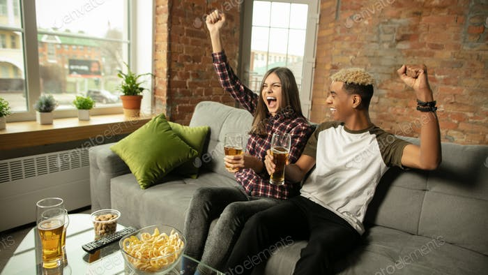 Excited couple, friends watching sport match, championship at home