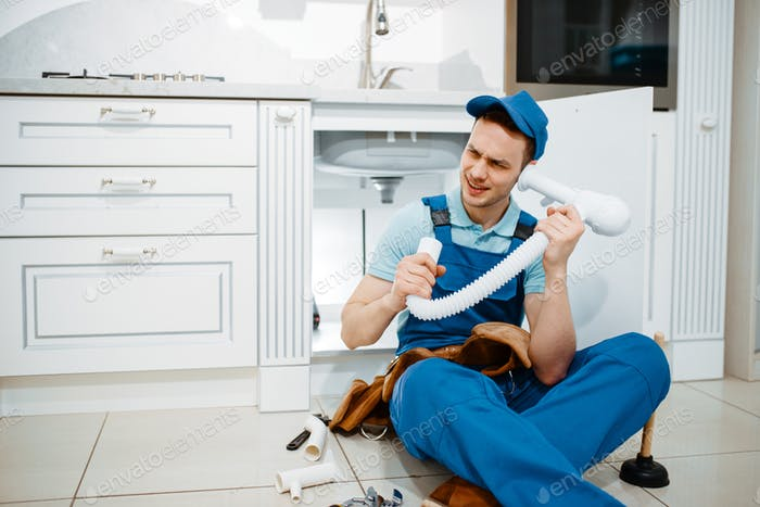 Male plumber listerns to the drain pipe, humor