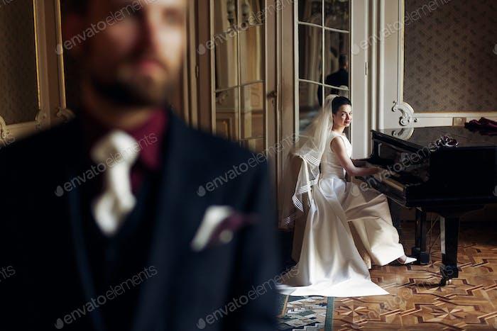 элегантная великолепная невеста играет фортепиано и стильный красивый жених позирует