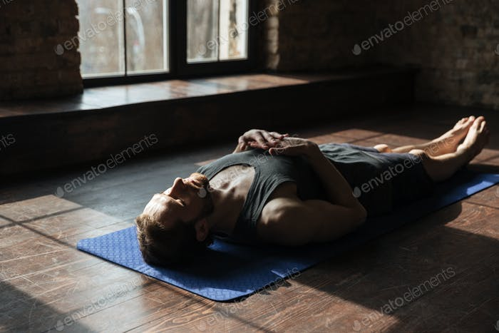 Handsome young strong sportsman in gym lies on floor