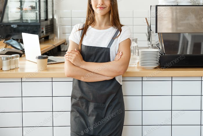 Coffee Business owner Concept - attractive young beautiful caucasian barista in apron smiling at