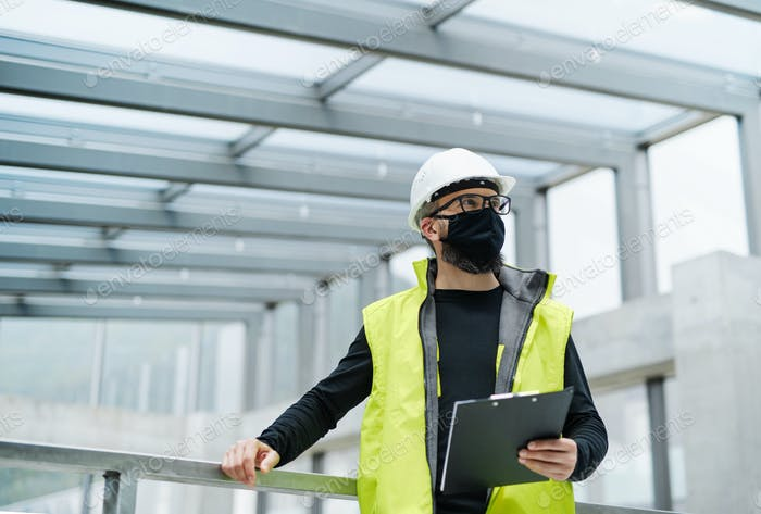 Portrait of worker with face mask at the airport, holding clipboard