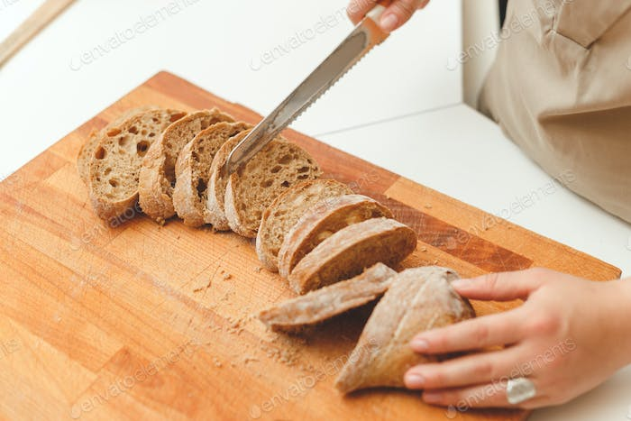 Woman cutting a bread ciabatta with knife in kitchen