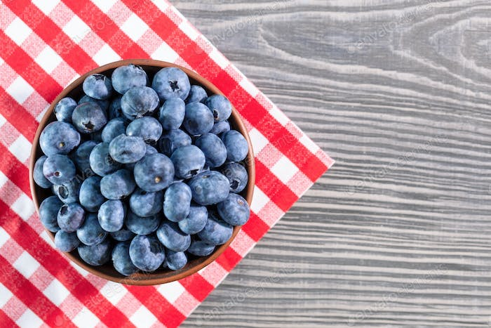 Blueberries in clay bowl on table with red checkered tablecloth