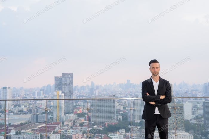 Portrait of businessman standing on the rooftop of a skyscraper with copyspace