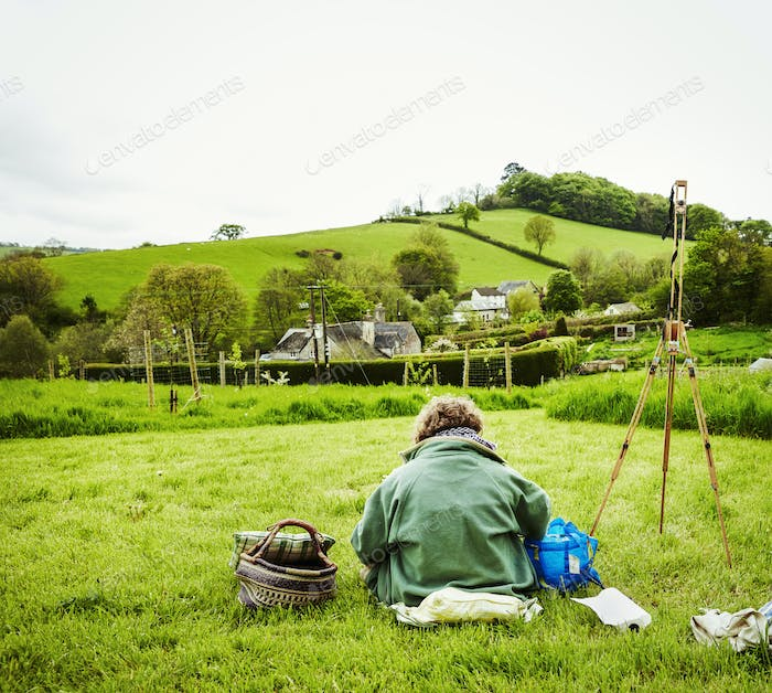 A woman artist working outdoors in the landscape, sitting on the ground, back view.