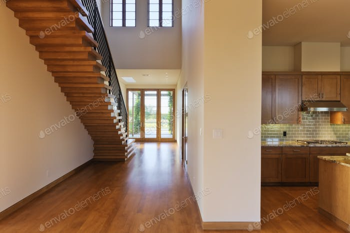 Spacious Hallway Showing a Staircase and Modern Kitchen