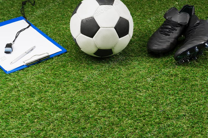 close up of clipboard with soccer ball and boots on grass pitch
