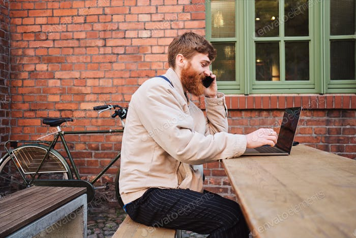 Young bearded man happily talking on cellphone working on laptop in cafe on street