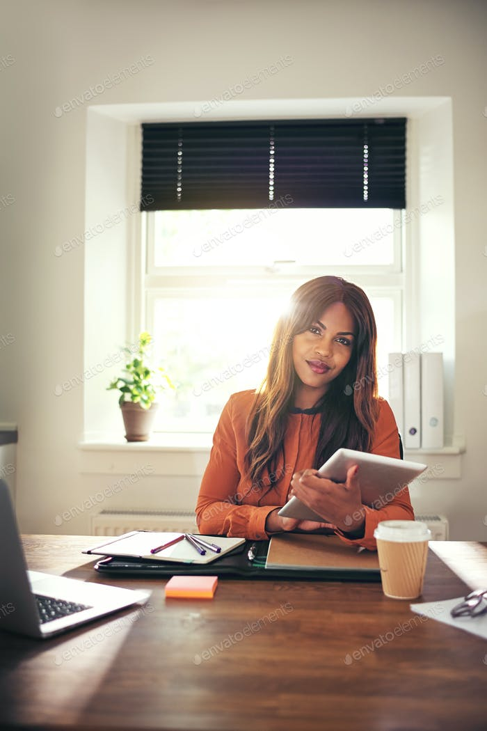 Confident young woman using a tablet in her home office