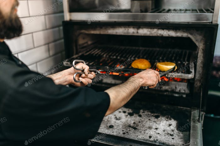 Male cook prepares tasty burger on grill oven