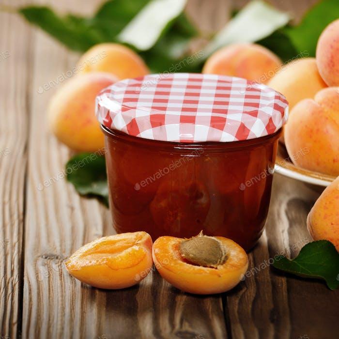 Glas Aprikosenmarmelade auf Holztisch mit reifen Aprikosen asid