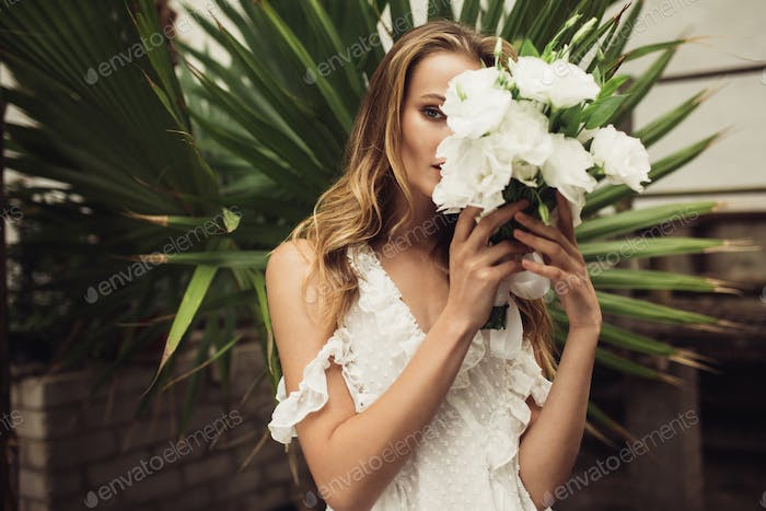 Young beautiful woman in white dress covering face with little b