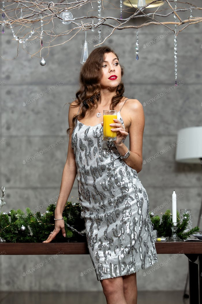 Pretty brunette girl in a shining gray evening dress holding a glass of juice is standing next to