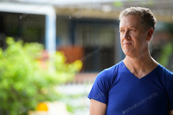 Mature man thinking while looking away in the streets outdoors