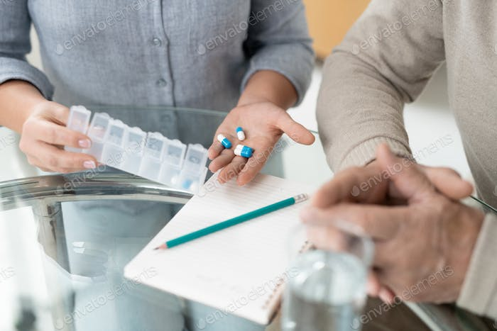 Hands of young woman holding pills while showing medicine to sick senior father