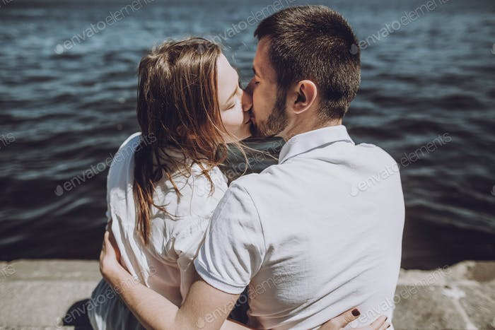 modern woman and man in fashionable white clothes embracing, sensual romantic moment