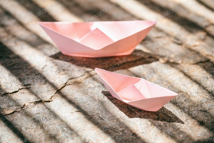 Pink paper folded, origami, boats on a rock