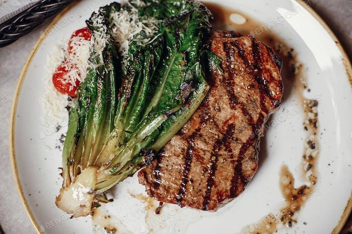 Köstliches gegrilltes saftiges Steak mit geröstetem Kohl, Tomaten und Käse