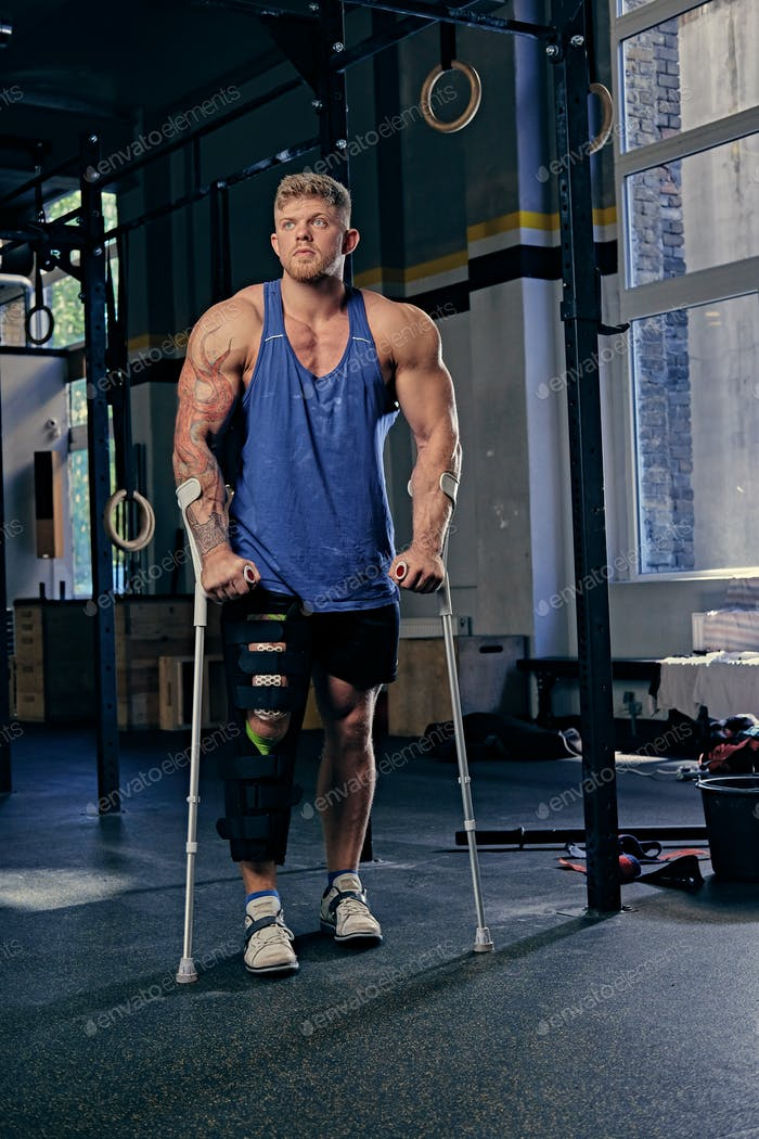Bodybuilder on crutches in a gym club.