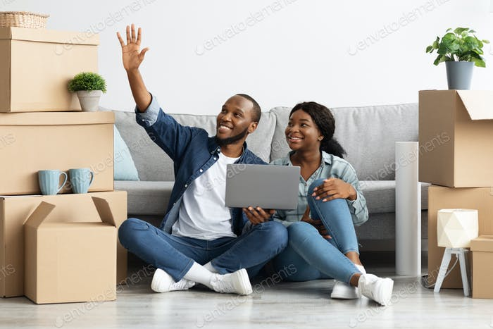 Happy Black Couple Sitting With Laptop And Imagining Design In Their Flat