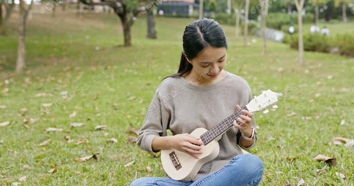 Young Woman play on ukulele at the park