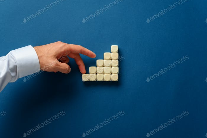 Businessman walking his fingers up the stairs made of wooden dices