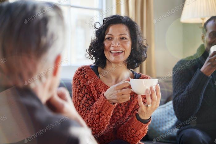 Mujer de mediana edad reunión Amigos alrededor de mesa en cafetería